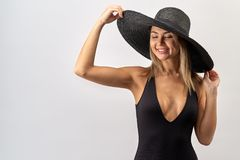 Large contrast Studio portrait of an attractive Caucasian woman with long blond hair in black bikini and hat royalty free stock photo