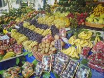 Large counter in the market with a variety of fruits and berries royalty free stock photo