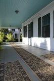 Large covered front porch. A large outdoor front porch.  The floor is wood which is painted and has been covered with carpets.  The exterior of the house is Stock Images