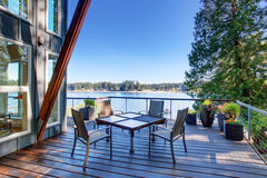 Large covered and furnished porch of luxury house with view of the lake royalty free stock photo