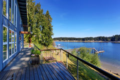 Large covered porch of luxury home with lake view. Royalty Free Stock Image