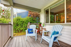 Large covered porch with railings and outdoor seats. Large covered porch with railings ,outdoor seats, flower pots. Northwest, USA Royalty Free Stock Photography