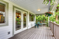 Large covered porch with railings and outdoor seats. Large covered porch with railings ,outdoor seats, flower pots and turned on lights on the ceiling. Northwest Royalty Free Stock Photography