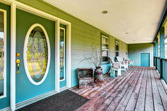 Large covered porch with white chairs and turquoise front door. Northwest, USA Royalty Free Stock Image