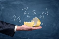 A large cracked and empty golden egg lying on a businessman`s palm with negative arrows drawn on a chalkboard around it. Golden goose. Loss of money. Profit Royalty Free Stock Photo