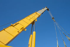 Large crane jib against blue sky background Stock Photos