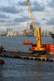 A large crane removing containers from a ship at the Cartagena Harbor Dock stock image