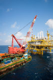 Large crane vessel installing the platform in offshore,crane barge doing marine heavy lift. Installation works in the gulf or the sea stock images