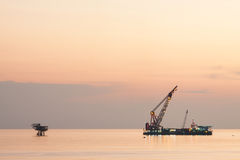Large crane vessel installing the platform in offshore,crane barge doing marine heavy lift installation works. In the gulf or the sea stock photos