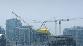 Large Cranes In City With Snow Falling stock footage