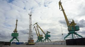 Large cranes move loads. Port cranes for unloading sand on ship stock footage