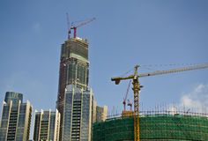 Large cranes next to high rise buildings under construction. Tall tower crane on construction site with blue sky background Royalty Free Stock Photo