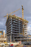 Large cranes working in construction site building new office bu Royalty Free Stock Images