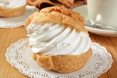 Large cream puff. A large golden cream puff on a doily with a cup of coffee Stock Images