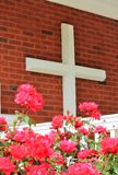 Large Cross with Pink Flowers. A large white cross mounted on the front of a church, with pink flowers in front Stock Photo