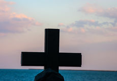 A large cross stands on the background of the sea Stock Images