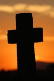 Large cross at sunset. A Christian cross silhouetted against an orange sunset Stock Images