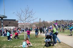 A large crowd of adults and children flying kites at the Kite Festival on the National Mall. WASHINGTON, DC - March 31, 2018: A large crowd of adults and Royalty Free Stock Images