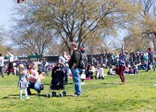 A large crowd of adults and children flying kites at the Kite Festival on the National Mall. WASHINGTON, DC - March 31, 2018: A large crowd of adults and Royalty Free Stock Photography