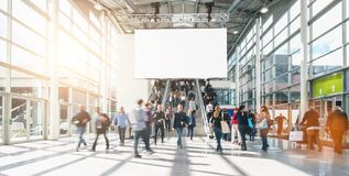 Large crowd of anonymous blurred people at a trade show, including copy space banner. People rushing at a entrance at a trade show, including banner with copy stock photo