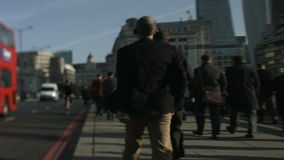 Large crowd of pedestrians walk over London Bridge 41a Royalty Free Stock Images