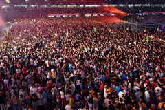 Large crowd of people at a concert in the front of the stage. CLUJ-NAPOCA, ROMANIA - AUGUST 7, 2016: Large crowd of people, audience partying in the front of the Stock Photography
