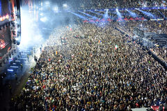 Large crowd of people at a concert in the front of the stage. CLUJ-NAPOCA, ROMANIA - AUGUST 7, 2016: Large crowd of people, audience partying in the front of the Royalty Free Stock Image