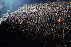 Large crowd of people at a concert in the front of the stage. CLUJ-NAPOCA, ROMANIA - AUGUST 7, 2016: Large crowd of people, audience partying in the front of the Stock Photo