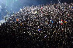 Large crowd of people at a concert in the front of the stage. CLUJ-NAPOCA, ROMANIA - AUGUST 7, 2016: Large crowd of people, audience partying in the front of the Royalty Free Stock Photo