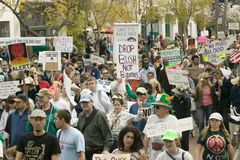 A large crowd of protesters march and chant down State Street carrying signs at an anti-Iraq War protest march in Santa Barbara, C Stock Photography