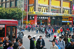 Large crowds of people moving past a McDonalds Store in China Stock Image