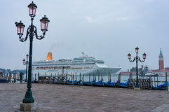 Large cruise liner Oriana at Venice bay. Venice, Italy - September 28, 2013: Oriana cruise liner on Grand Canal at early morning with parked gondolas and San Royalty Free Stock Photos