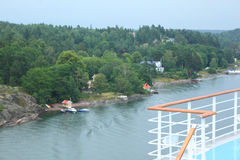 Large cruise ship deck near village. Focus on ship royalty free stock photos