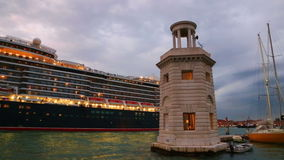 Large cruise ship sailing in the evening on the Grand Canal in Venice. Queen Elizabeth cruise liner enters the water area of the Venetian lagoon stock footage