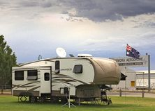Large cruiser caravan parked in Temora campground, beside the aerodrome. Large, luxury caravan/RV parked on the grass in Temora camp ground, aerodrome sign and royalty free stock images