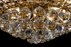 Large crystal chandelier close-up in baroque style isolated on black background. Stock Image