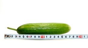 Large cucumber and a measuring tape on white. Large banana and measuring tape on white background Stock Images