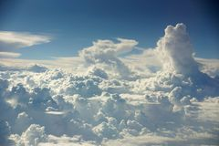 Large cumulus fluffy clouds from the window of an airplane at high altitude Royalty Free Stock Photo