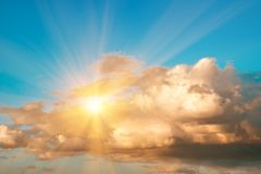 Large cumulus storm clouds and sun in the blue sky. Natural background stock photography