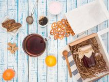 Transparent cup of black tea, cookies and lemon on a wooden table. Large cup of black tea, a lemon and a bag of cookies on an old wooden table in French style Stock Images