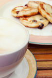 Large cup of cappuccino and cottage cheese pancakes with raisin; selective focus. Large cup of cappuccino and freshly baked cottage cheese pancakes with raisin Royalty Free Stock Image