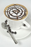 Large cup of coffee decorated with milk froth and chocolate draw Royalty Free Stock Photo