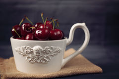 A large cup of coffee in front angel, white bowl full with fresh cherries, fruits. Dark rustic background, shabby chic, vintage ti Stock Photos
