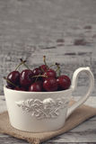 A large cup of coffee in front angel, white bowl full with fresh cherries, fruits. Light rustic background, shabby chic, vintage t Stock Images