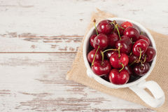 A large cup of coffee in front angel, white bowl full with fresh cherries, fruits. Light rustic background, shabby chic, vintage t Stock Photography