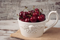 A large cup of coffee in front angel, white bowl full with fresh cherries, fruits. Light rustic background, shabby chic, vintage t Royalty Free Stock Images