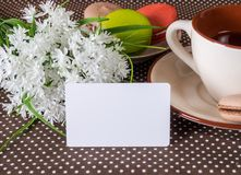 Large cup, white flowers and cakes. White card for applying text Royalty Free Stock Photos