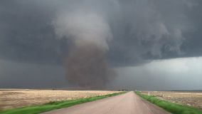 A large dangerous tornado lofts dirt high into the sky underneath a dark storm cloud. Footage shot from inside a vehicle driving towards the tornado stock video