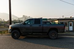 Large dark gray 4x4 pickup at sunrise in Gold Beach stock photography