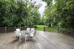 Large deck with chairs and table. Large wooden deck with table and chairs leading to backyard Stock Image
